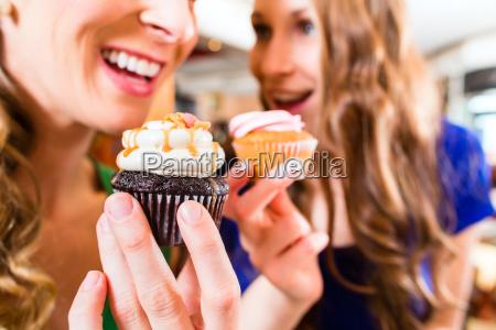 mulheres que comem bolinhos enquanto bebe