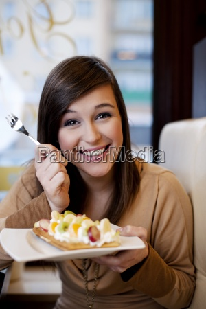 young woman eating waffles with whipped