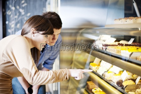 young woman pointing on cakes in