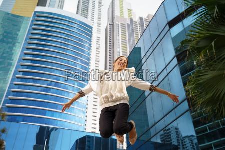 latina business woman jumping joy happy