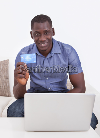 african man with credit card and