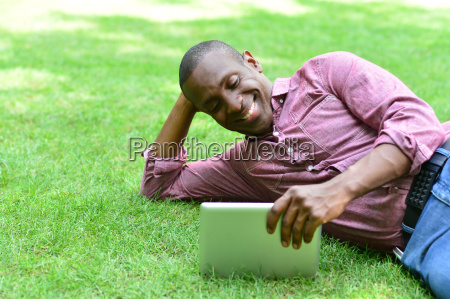 smiling man lying on the lawn