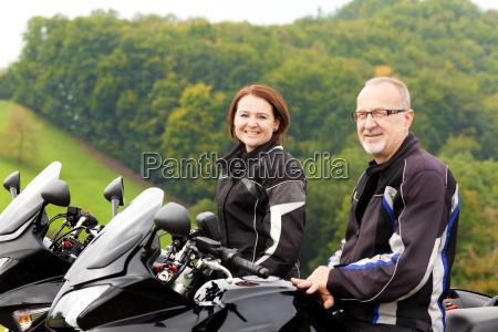 dois motociclistas sentam se feliz na