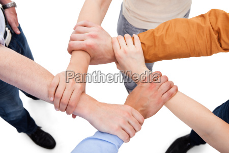 friends linking hands in team