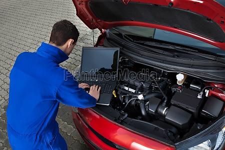mecanico usando o portatil ao reparar