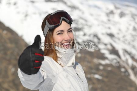 mulher de esquiador positiva gestos polegar