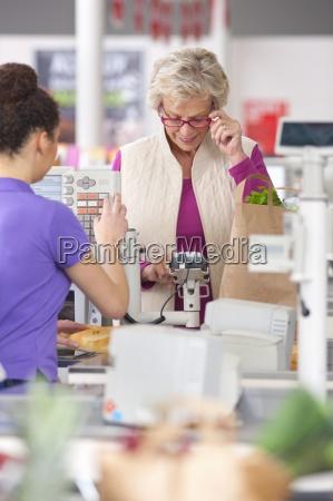 mulher idosa pagar para fazer compras