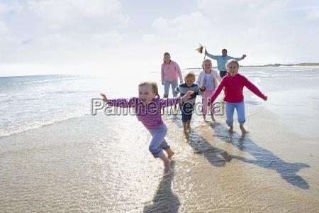 junge glueckliche familie am strand laufen