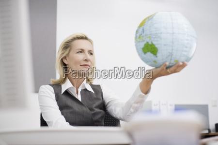 a businesswoman w biurze trzyma kule