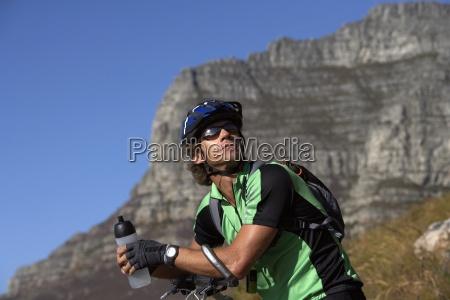 macho montanha motociclista sentando bicicleta olhar