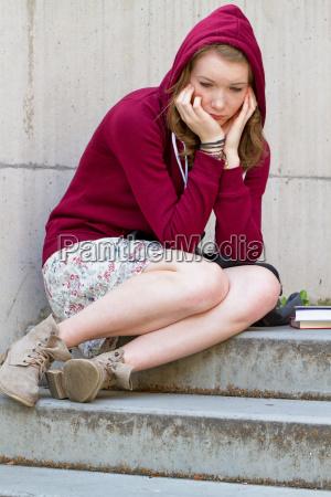 estudante triste em uma escadaria