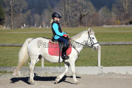 young girl riding on horse