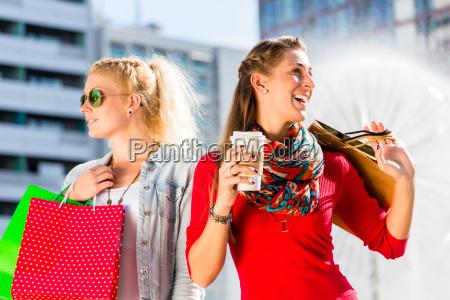 kvinder shopping i byen med poser