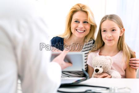 menina no medico com sua mae