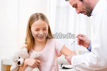 jovem menina sendo vacinada no medico
