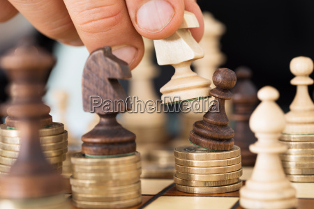mao jogando xadrez empilhada em moedas