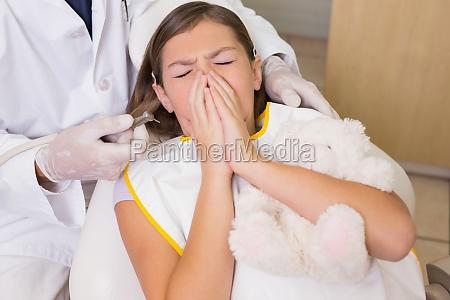 dentista pediatrico tentando ver dentes pacientes