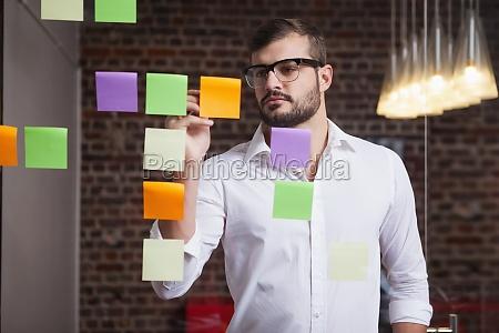 empresario casual escribiendo en notas adhesivas