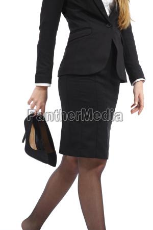business woman walking holding heels in