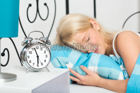 young blond woman lying in bed