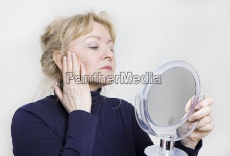 mulher idosa olha no espelho