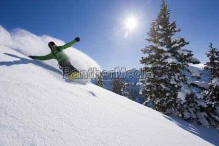 um snowboarder fazendo algumas faixas frescas