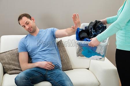homem ignorando roupas sujas segurando por