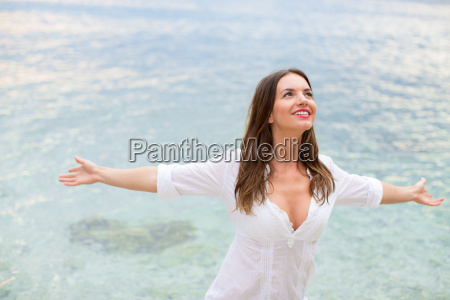 mulher que relaxa na praia com