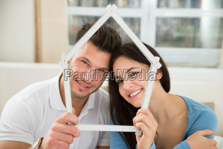 young couple with model house made