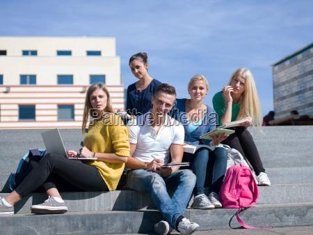 estudantes fora sentando se em etapas