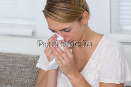 woman using tissue while suffering from