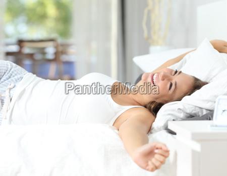 menina que acorda esticando os bracos