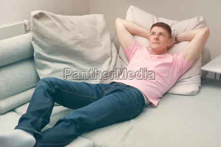 homem deitado no sofa