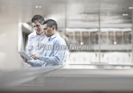 dois homens colegas de trabalho olhando
