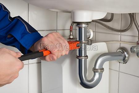 homem plumber reparacao sink no banheiro
