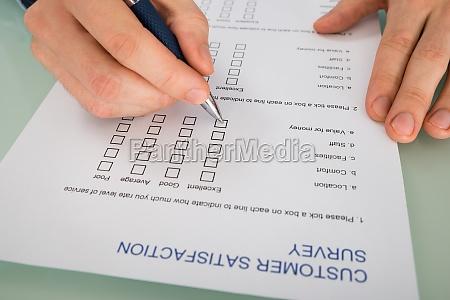 pessoa mao preenchendo formulario de satisfacao