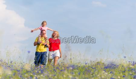 familia esta andando no prado com