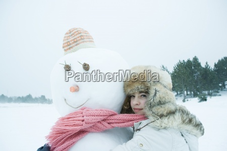 teen girl sharing scarf with snowman