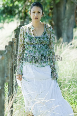 young woman walking beside rural fence