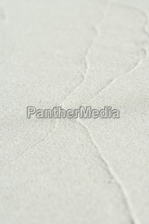 traces of surf on sand at
