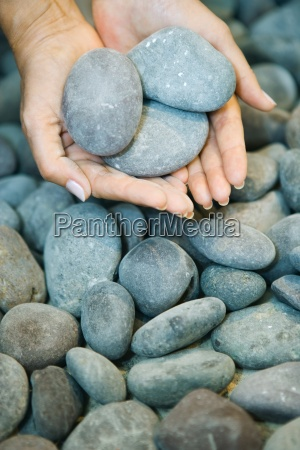 hands holding pebbles close up