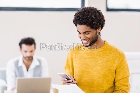 smiling man holding document using smartphone