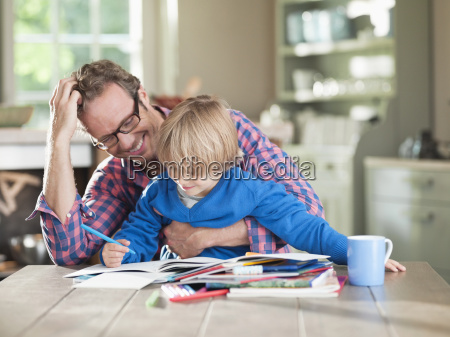 father and son doing homework at