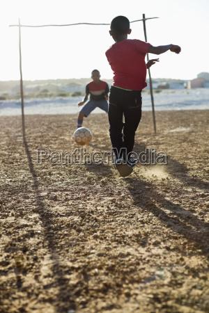 meninos que jogam o futebol junto