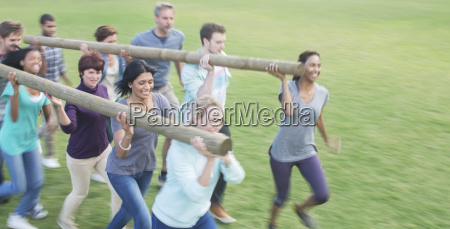 teams racing with logs in field