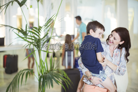 mother carrying son in hotel lobby