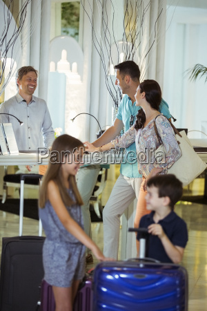 family with suitcases talking with receptionist