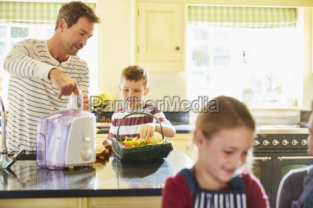 father and son juicing vegetables in