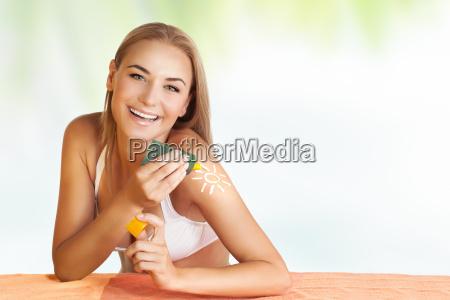 mulher feliz que aplica a proteccao