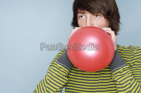 teenage boy blowing red balloon in